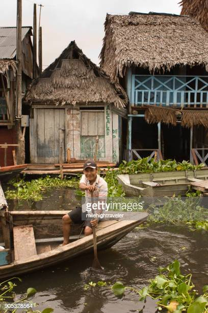 Smiling Amazon River boatman paddles past thatched roofs homes shops Iquitos Peru