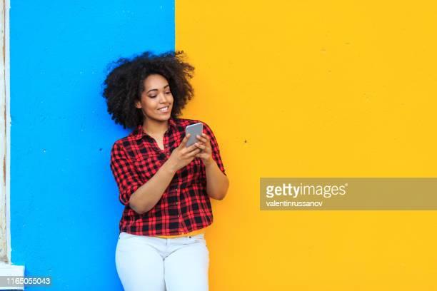 femme american-african de sourire écoutant la musique sur le téléphone intelligent - une seule jeune femme photos et images de collection