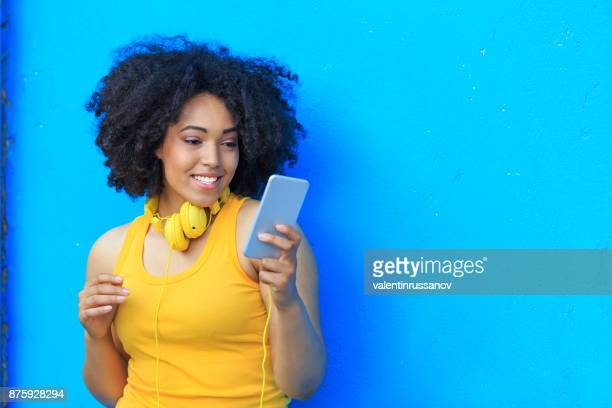 smiling american-african woman listening music on smart phone - bright blue background stock pictures, royalty-free photos & images
