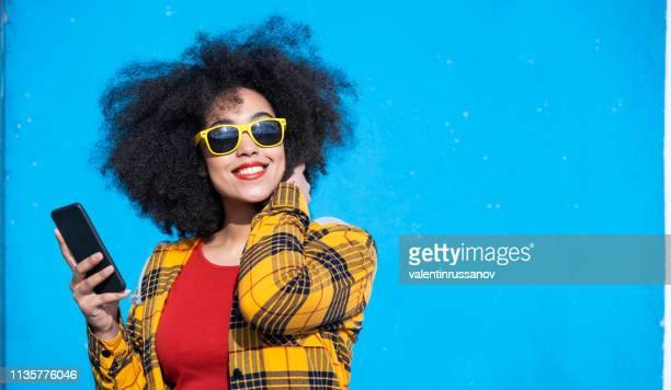 mulher americano-africana de sorriso que usa o telefone esperto em um fundo azul - colorido - fotografias e filmes do acervo