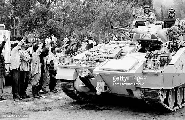 Smiling and cheering crowds of Iraqis welcome the liberating British forces as they enter Basrah