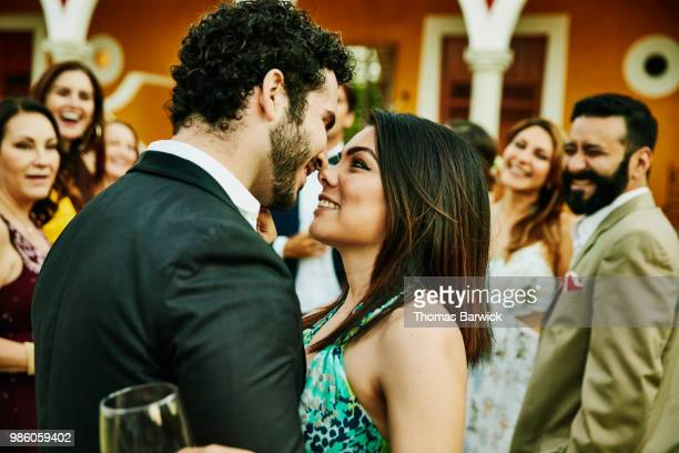 smiling and embracing couple about to kiss during outdoor wedding reception - wedding guest stock pictures, royalty-free photos & images