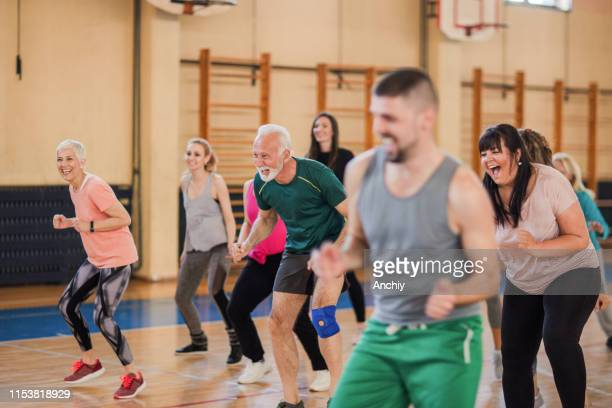 smiling and happy group of people dancing at gym - sports training stock pictures, royalty-free photos & images