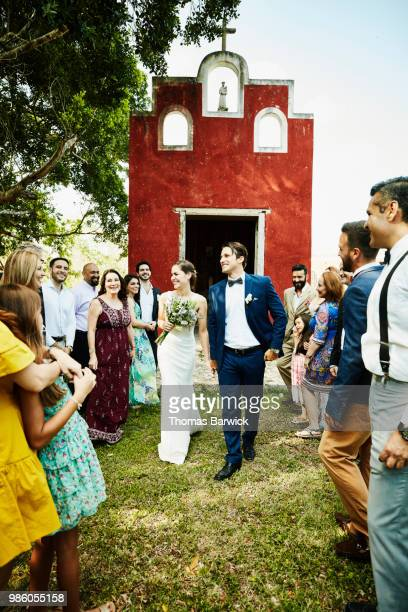 smiling and laughing bride and groom walking past wedding guests after being married in chapel - wedding guest stock pictures, royalty-free photos & images