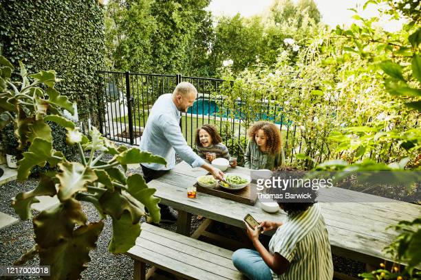 smiling and laughing family sharing meal at picnic table in backyard - four people stock pictures, royalty-free photos & images