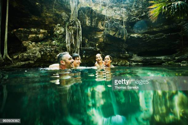 Smiling and laughing family swimming together in cenote during vacation
