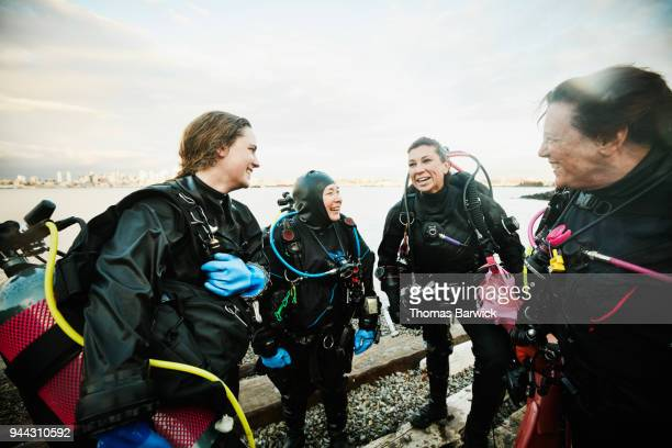 Smiling and laughing female divers in discussion on shoreline after open water dive