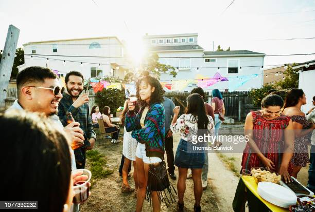 smiling and laughing friends hanging out together during backyard barbecue on summer evening - men friends beer outside stock pictures, royalty-free photos & images