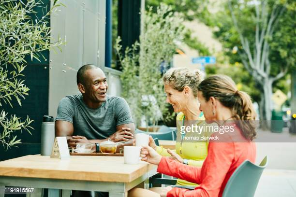 smiling and laughing friends in discussion at outdoor cafe after morning run - カーキグリーン ストックフォトと画像
