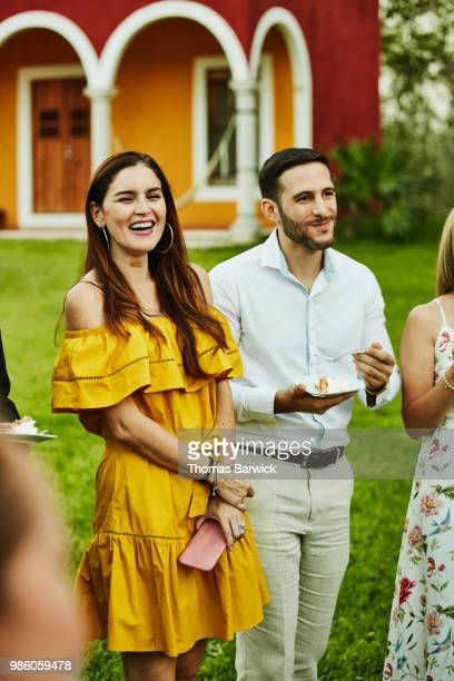 smiling and laughing friends listening to wedding toast during outdoor reception at tropical resort - off shoulder stock pictures, royalty-free photos & images