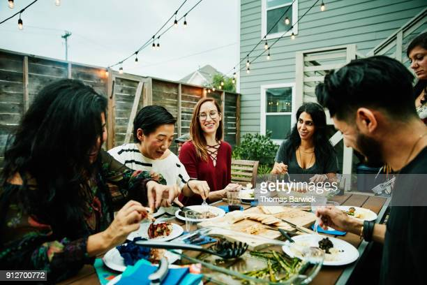smiling and laughing friends sharing dinner at table in backyard - dineren stockfoto's en -beelden