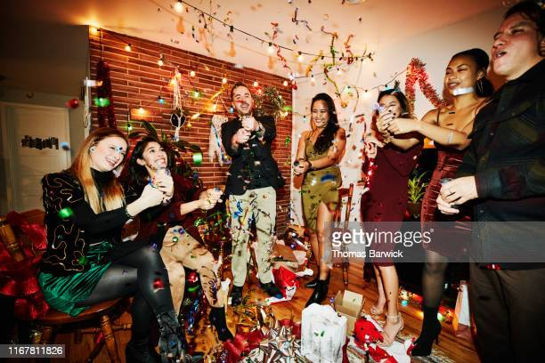 smiling and laughing friends shooting party poppers during holiday party in home - クラッカー ストックフォトと画像