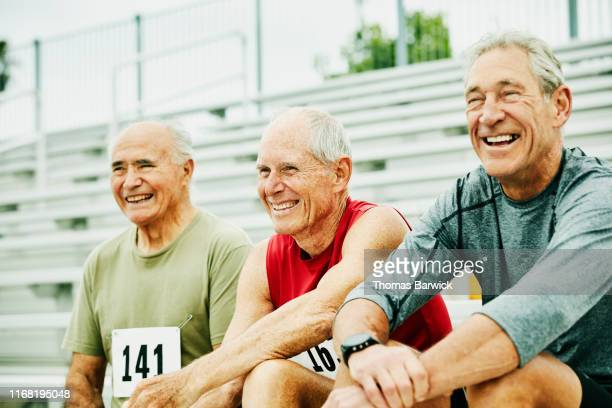 smiling and laughing senior male track athletes hanging out together on bleachers - sportsperson stock pictures, royalty-free photos & images