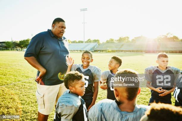 Smiling and laughing young football players in discussion with coach on football field after practice