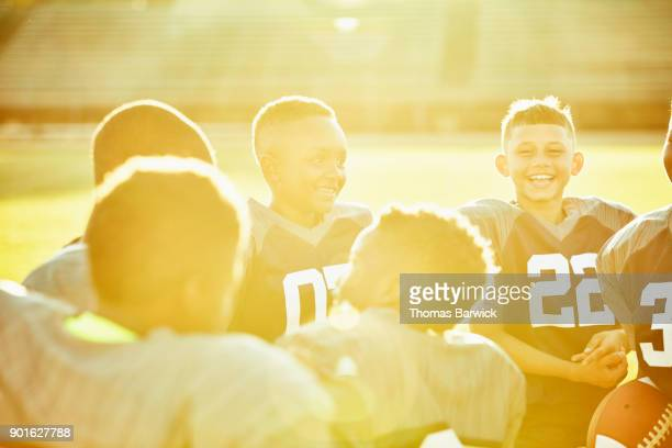 Smiling and laughing young football teammates gathered together in circle on field after game