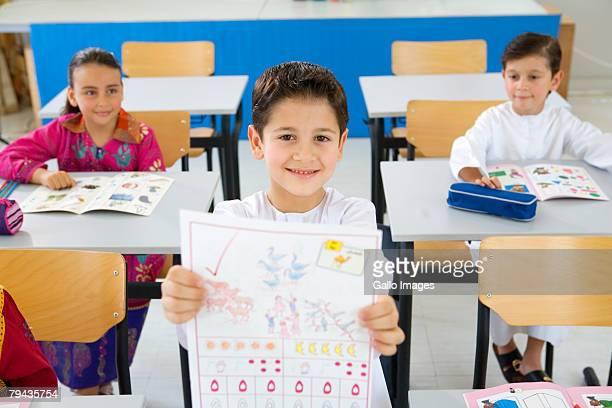 Smiling Arab boy holding up homework in classroom. Dubai, United Arab Emirates
