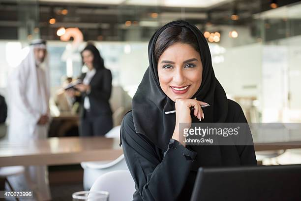 smiling arab businesswoman holding pen in office - united arab emirates stock pictures, royalty-free photos & images