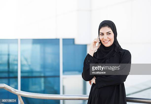 Smiling Arab Businesswoman Talking On Phone Outside Office