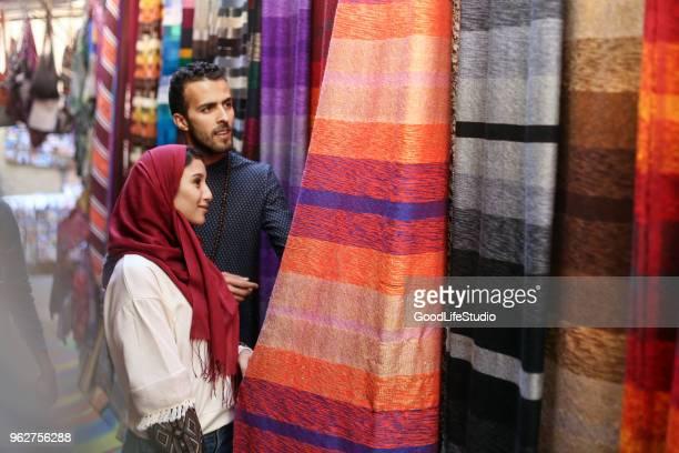 couple d'arabe souriante regardant tapis - homme marocain photos et images de collection