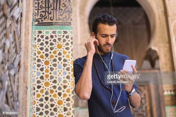 smiling arab man listening to music - north africa stock pictures, royalty-free photos & images