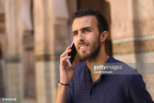 homme arabe parler téléphone mobile souriant - homme marocain photos et images de collection