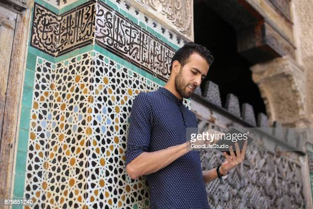 Smiling Arab man using tablet
