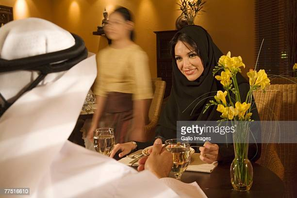 Smiling Arab Woman Looking Across Restaurant Table at Husband. Dubai, United Arab Emirates
