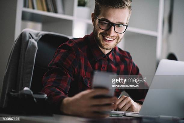 smiling architect checking his social media - mihailomilovanovic stock-fotos und bilder