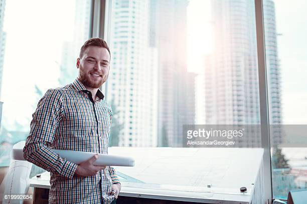 Smiling Architect Holding Blueprint Plans in His Office