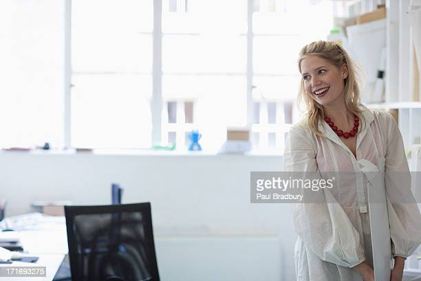 Smiling architect holding plans in office