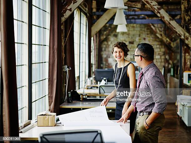 smiling architect leading project discussion - leanintogether stock pictures, royalty-free photos & images