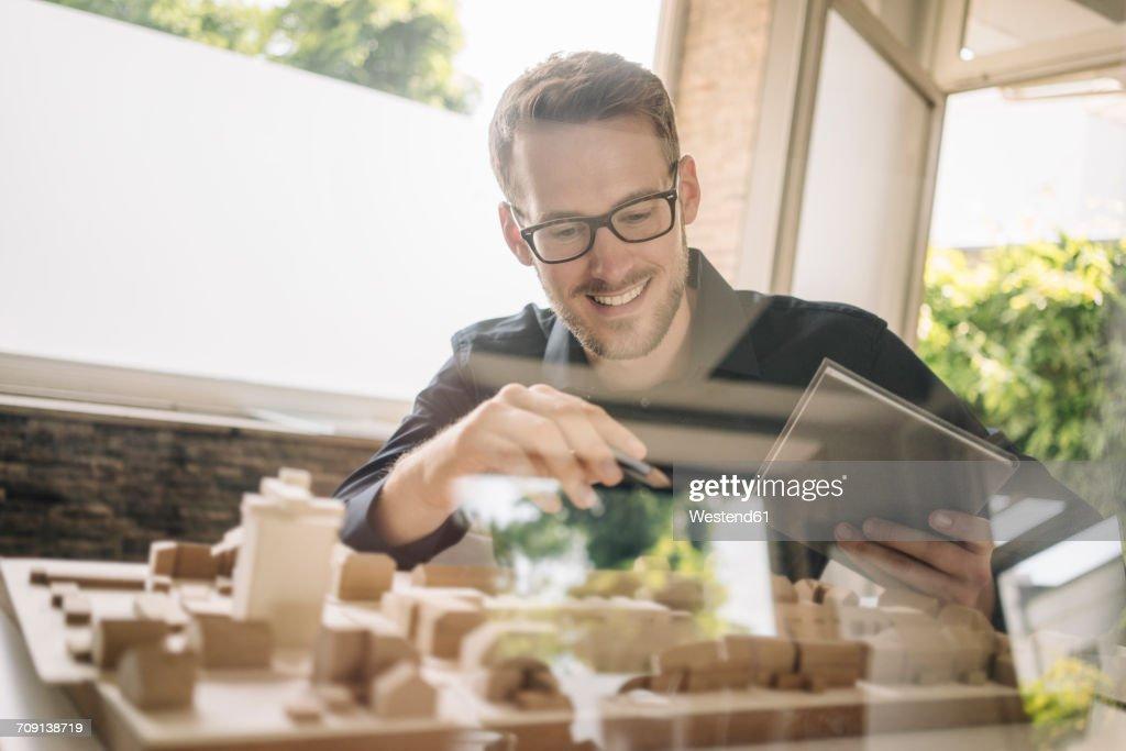 Smiling architect looking at urban development model : Stock-Foto