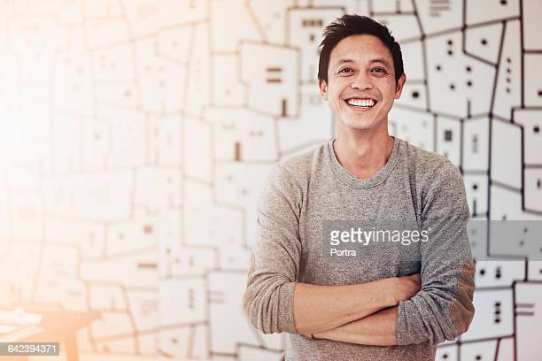 Smiling architect with arms crossed in office