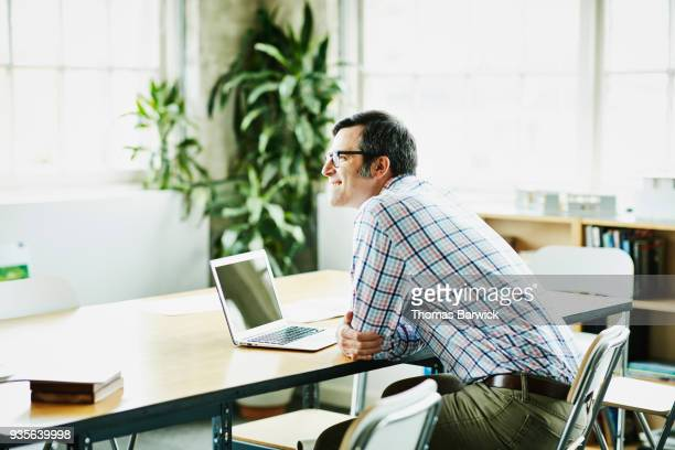 Smiling architect working at conference table in design studio