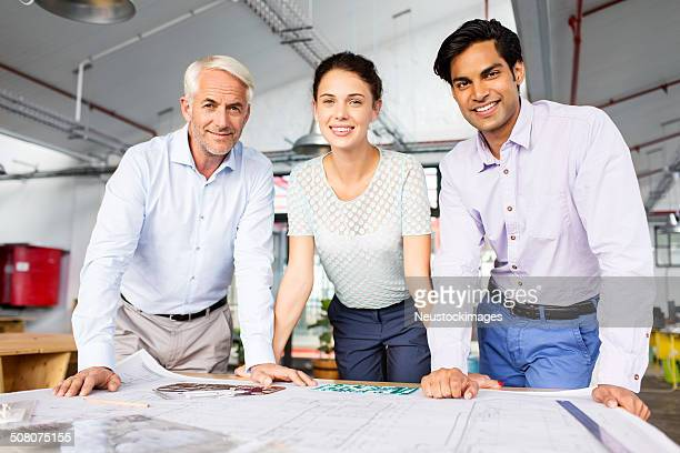 Smiling Architects With Blueprint At Office Desk