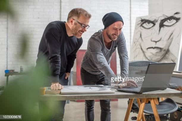 smiling artist using laptop with man in studio - art dealer stock pictures, royalty-free photos & images
