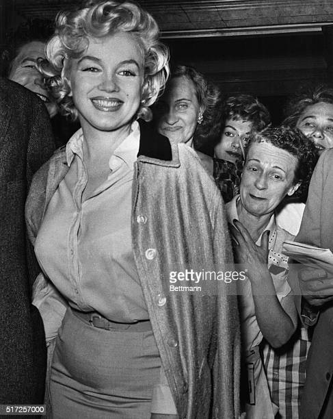 Smiling as a crowd clusters behind her, actress Marilyn Monroe leaves Lenox Hill Hospital here June 26th to recuperate at her home from gynecological...