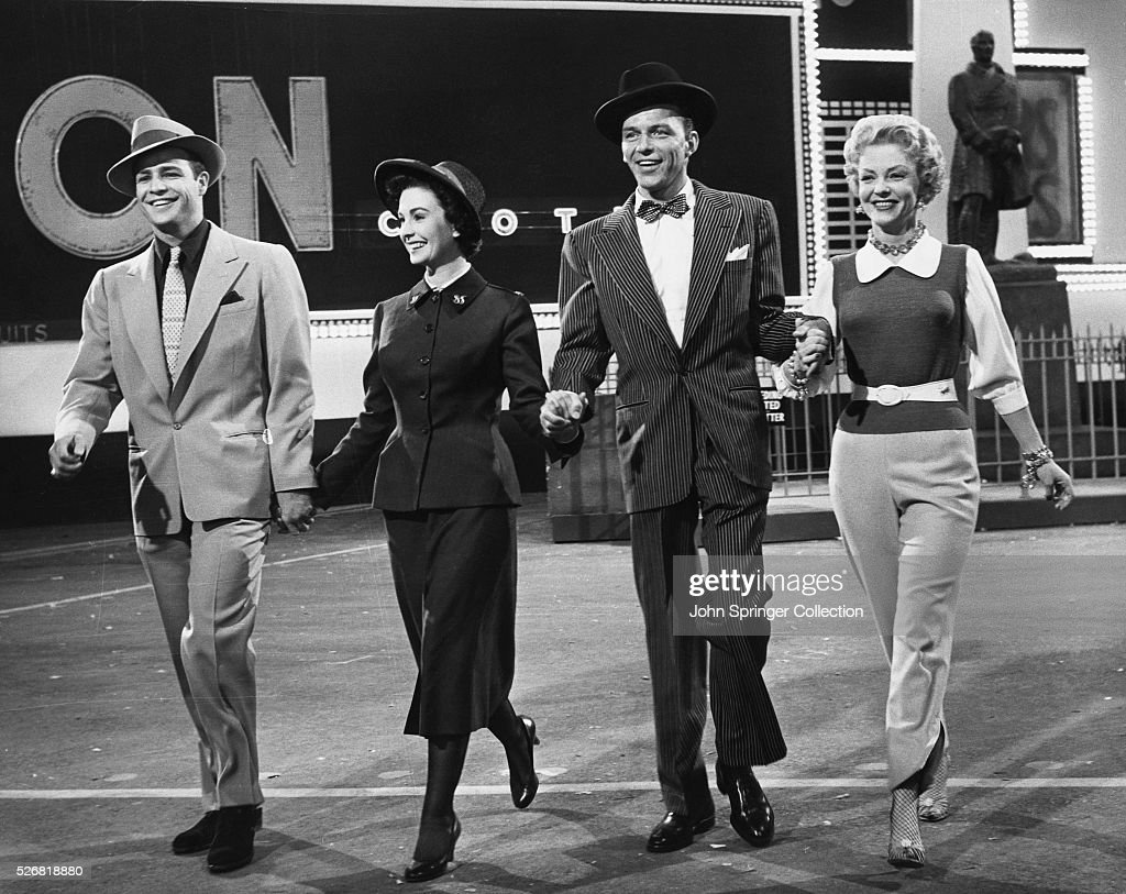Smiling as the walk hand in hand are, from left to right Sky Masterson (Marlon Brando), Sarah Brown (Jean Simmons), Nathan Detroit (Frank Sinatra), and Miss Adelaide (Vivian Blaine), in Guys and Dolls.