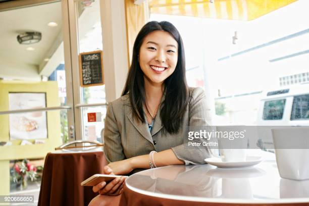 smiling asian businesswoman drinking coffee and holding cell phone - korean ethnicity stock pictures, royalty-free photos & images