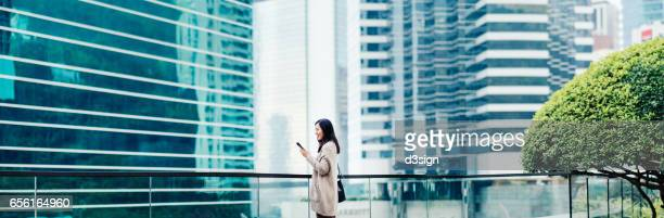 Smiling Asian businesswoman using mobile phone outdoors against urban cityscape
