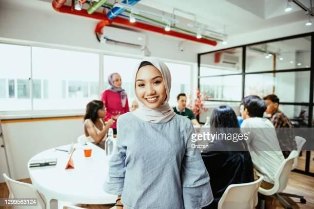 glimlachende aziatische onderneemster met hijab in bureau - zuidoost aziatische etniciteit stockfoto's en -beelden