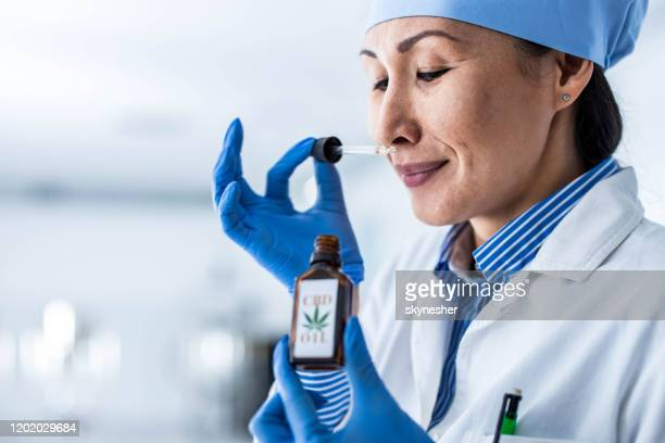 smiling asian chemist smelling cbd oil in laboratory. - cbd oil stock pictures, royalty-free photos & images