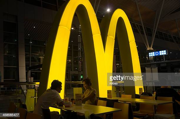 smiling asian couple eating in mcdonalds restaurant - mcdonald's stock photos and pictures