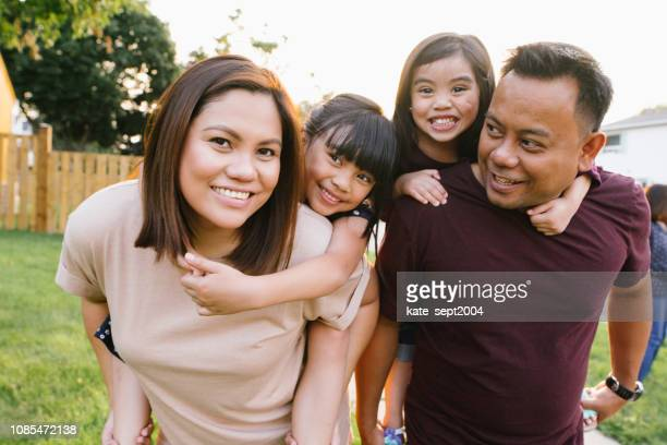 smiling asian family outdoor with two little kids - emigration and immigration stock pictures, royalty-free photos & images