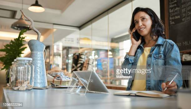 smiling asian female entrepreneur talking on a cellphone in her cafe - directrice photos et images de collection