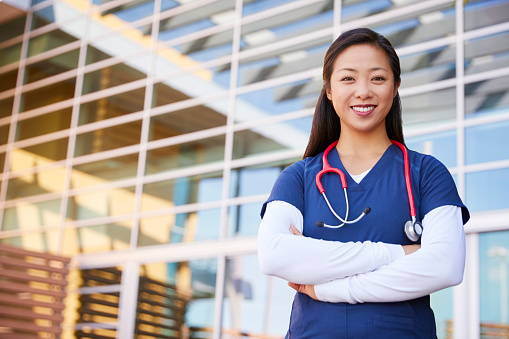 Smiling Asian female healthcare worker with arms crossed 998312932
