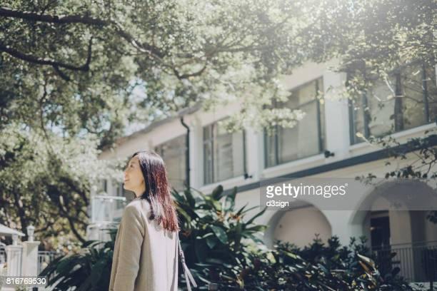 Smiling Asian girl walking and enjoying the nice weather in university campus