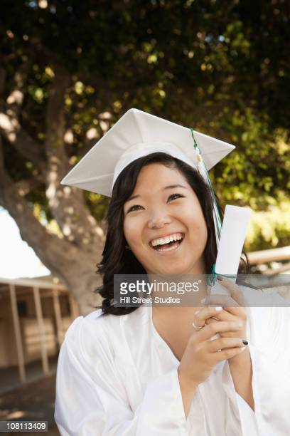 Smiling Asian high school graduate holding diploma