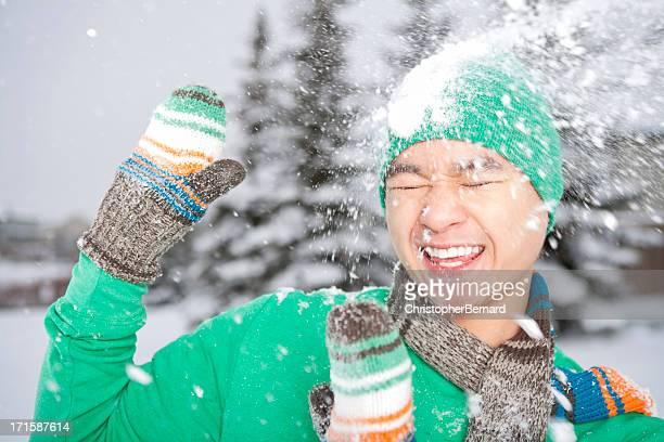 Souriant homme asiatique a atteint avec Boule de neige
