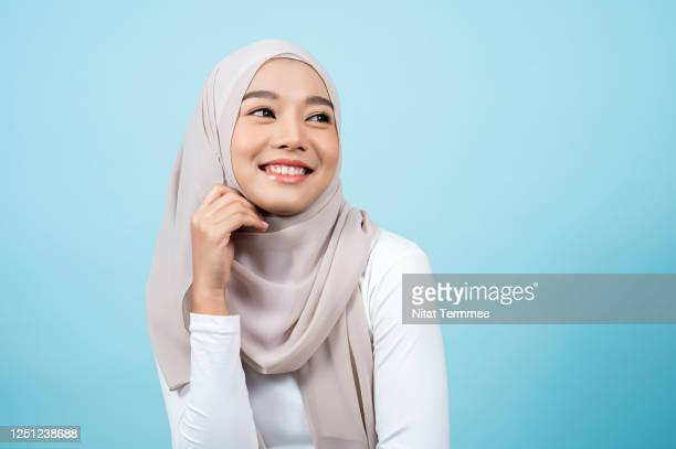 smiling asian muslim woman wearing headscarf while standing with a light blue background. muslim people concepts - ヒジャブ ストックフォトと画像